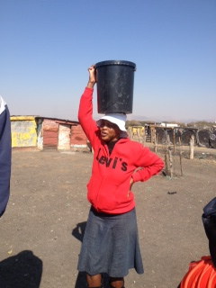 This is Emma, a Tapalogo (one of Serve's partners) 'Home- Based Care' Worker. Here she is pictured fetching water for a vulnerable lady living on her own who was too weak to get her own water. She works in Freedom Park and goes around patients' homes checking up on if they are too ill to come to the clinic and making sure they take their ARTs.