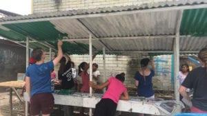 SERVE volunteers and Badjao vendor owners refurbishing the stalls together